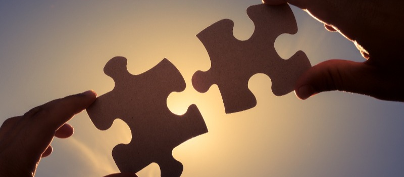 Hands joining two puzzle pieces